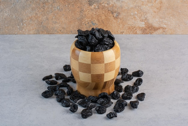 Zwarte droge sultanarozijnen of rozijnen in een houten kop.