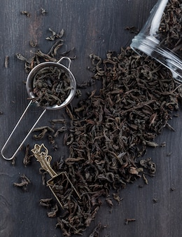 Zwarte droge thee in zeef, pot, lepel op een houten oppervlak plat leggen. Gratis Foto