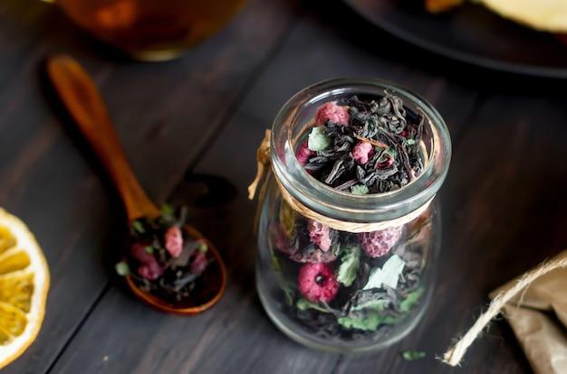 Zwarte droge thee met bladmunt en droge framboos in pot en houten lepel op donkere houten tafel, fruitsnack, honing en pastille gezellige theetijd. natuurlijk licht, selectieve focus