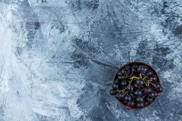 Zwarte druiven in een klei kom plat lag op een grungy gips achtergrond