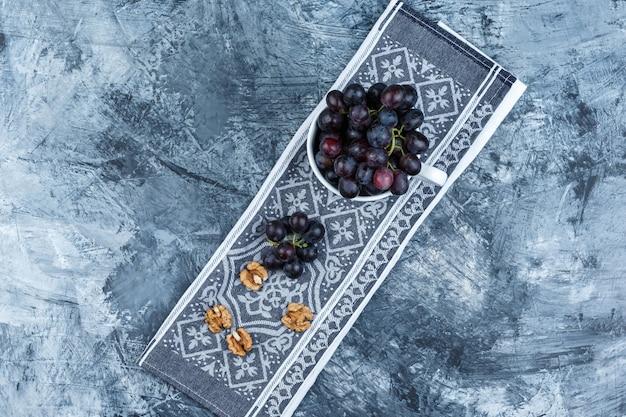 Zwarte druiven in een witte kop met walnoten bovenaanzicht op grunge en keuken handdoek achtergrond