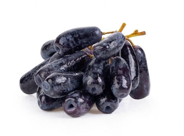 Zwarte druiven met druppel water dat op wit wordt geïsoleerd