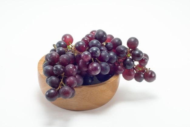 Zwarte druiven worden geplaatst in een houten kop tegen een witte achtergrond.