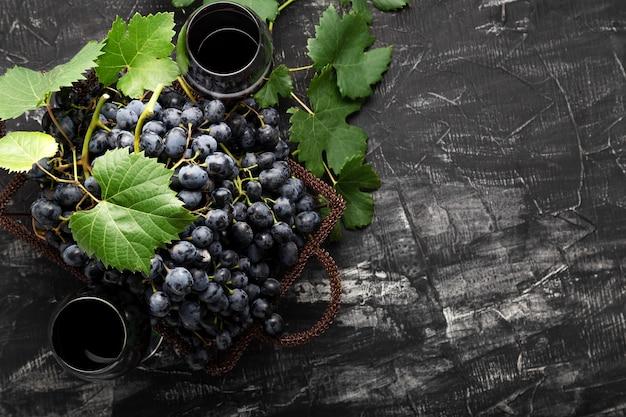 Zwarte druivenmand en glas rode wijn op donkere rustieke betonnen achtergrond. platte wijnsamenstelling rode wijnglas of druivensap op zwarte stenen tafel met kopieerruimte.