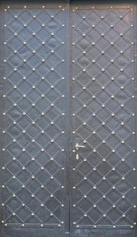 Zwarte dubbele metalen deuren met ruitvormig patroon en klinknagels.