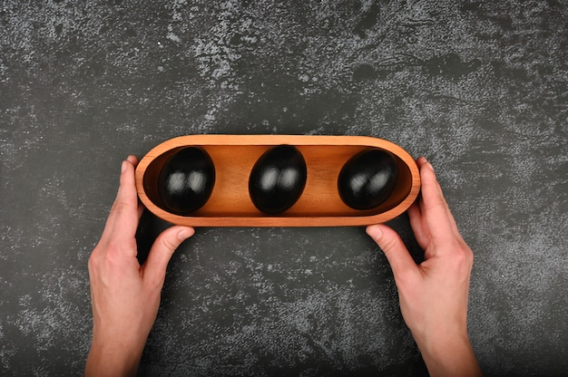 Zwarte eieren in de handen. plat lag. zwarte pasen. drie zwarte eieren