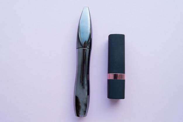 Zwarte elegante lippenstift en mascarabuizen op roze. make-up en schoonheid concept
