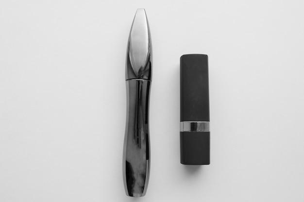 Zwarte elegante lippenstift en mascarabuizen op wit. make-up en schoonheid concept