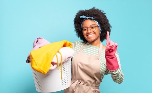 Zwarte en afrovrouw die vriendelijk glimlacht kijkt, nummer één toont of eerst met vooruit hand, aftellend.
