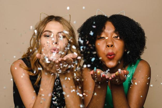 Zwarte en blanke mooie jonge vrouwen confetti blazen in de camera op een beige achtergrond.