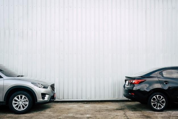 Zwarte en bronzen kleurenwagens die op concrete vloer met metaalplaatmuur parkeren