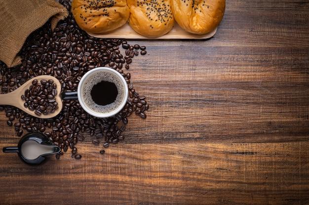 Zwarte en bruine koffiebonen met kop warme drank en brood op houten tafel, bovenaanzicht kopie ruimte