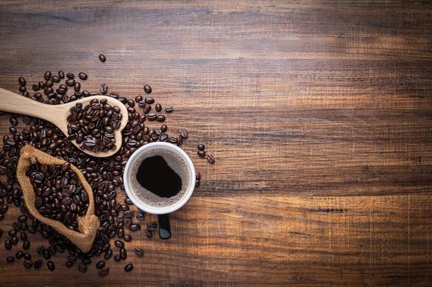 Zwarte en bruine koffiebonen met kop warme drank op houten tafel, bovenaanzicht kopie ruimte
