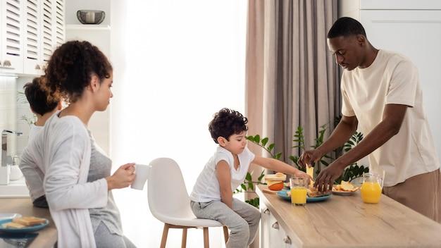 Zwarte en gelukkige familie die de tafel dekt om te eten