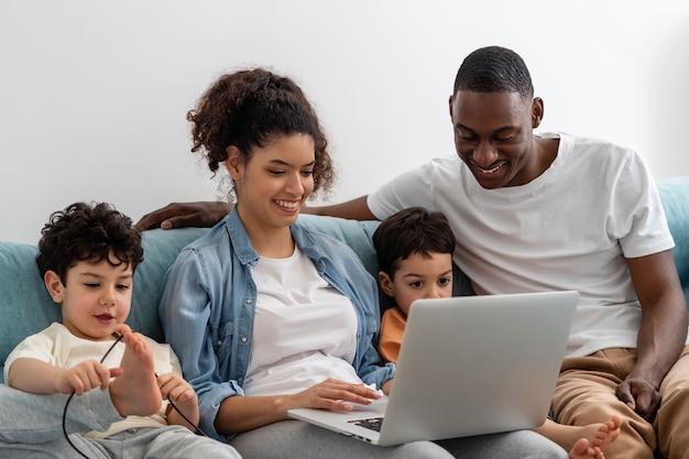 Zwarte en gelukkige familie kijken met plezier tijdens het kijken naar iets op laptop