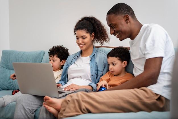 Zwarte en gelukkige familie kijken naar een film op laptop