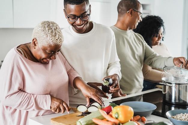 Zwarte en gelukkige familie koken in de keuken thuis - vader, dochter, zoon en moeder met plezier bij het voorbereiden van lunch - belangrijkste focus op het gezicht van de jongen