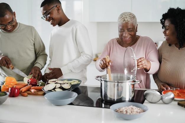 Zwarte en gelukkige familie veganistisch eten in de keuken thuis koken