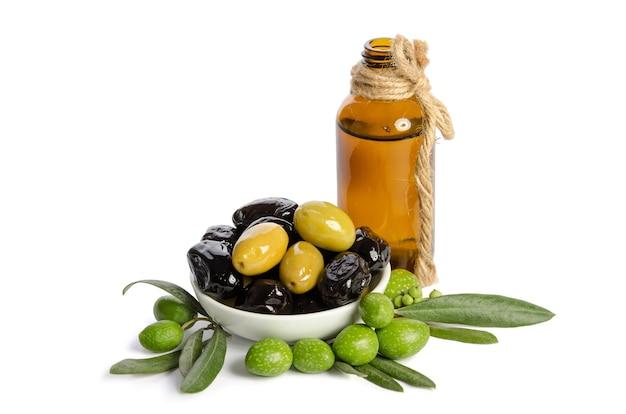 Zwarte en groene olijven gemengd in de porseleinen kom en olijfolie van eerste persing