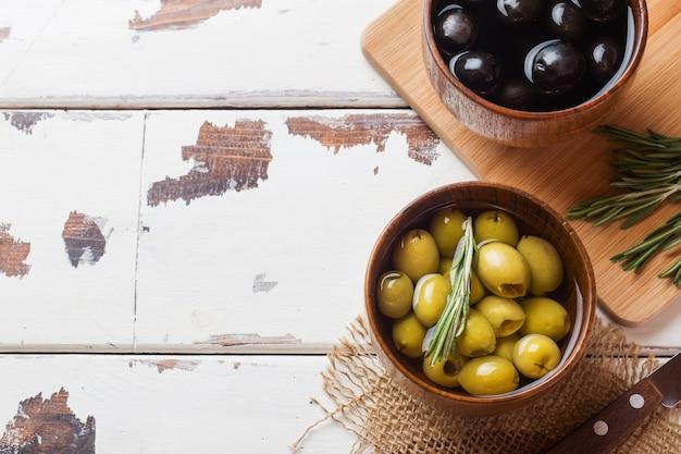 Zwarte en groene olijven in houten kommen op houten tafel. bovenaanzicht met ruimte voor tekst.