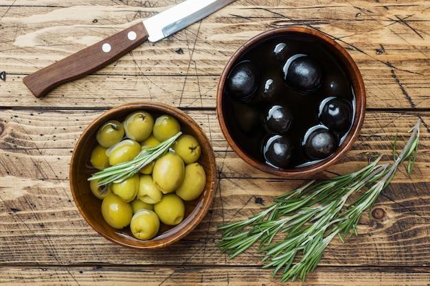 Zwarte en groene olijven in houten kommen op houten tafel