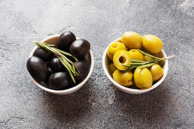 Zwarte en groene olijven in kommen op donkere tafel