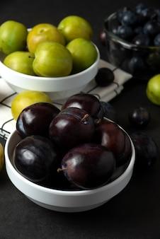 Zwarte en groene pruimen in witte ceramische schotel in de keuken