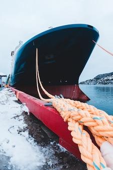 Zwarte en rode boot op watermassa overdag