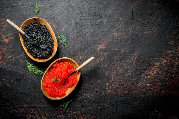 Zwarte en rode kaviaar in kommen met lepels en dille. op donkere rustieke ondergrond