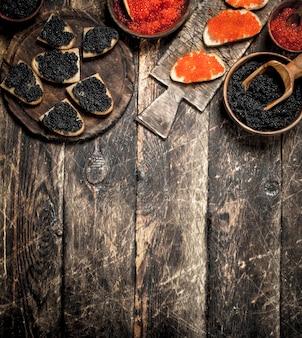 Zwarte en rode kaviaar in oude houten kommen. op houten achtergrond.