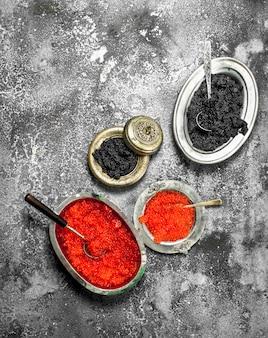 Zwarte en rode kaviaar in oude kommen. op rustieke achtergrond.