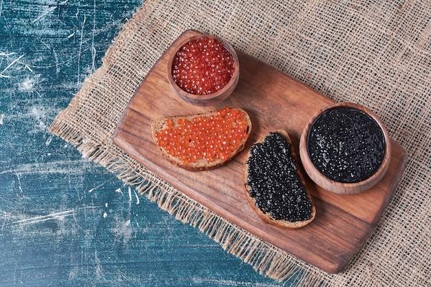 Zwarte en rode kaviaar op boterham.