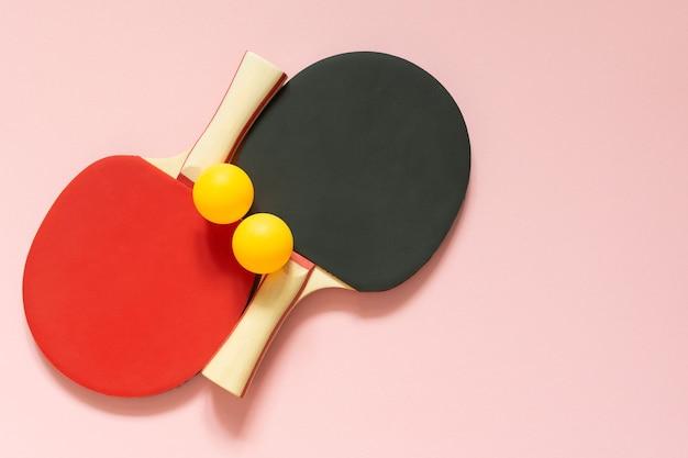 Zwarte en rode tennis pingpongrackets en oranje ballen geïsoleerd op een roze achtergrond, sportuitrusting voor tafeltennis