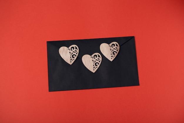 Zwarte envelop met drie houten harten op de rode achtergrond. valentijnsdag concept.