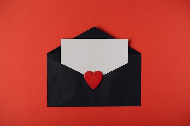 Zwarte envelop met een blanco vel binnen en een rood houten hart op de rode achtergrond. valentijnsdag concept. plat lag, bovenaanzicht.