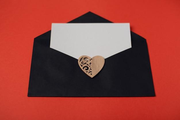 Zwarte envelop met een blanco vel papier en een houten hart op de rode achtergrond. valentijnsdag concept.