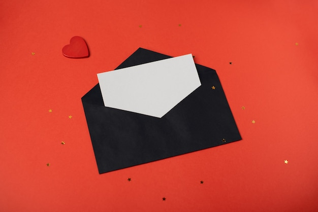 Zwarte envelop met een blanco vel papier en een rood hart op de rode achtergrond. valentijnsdag concept.
