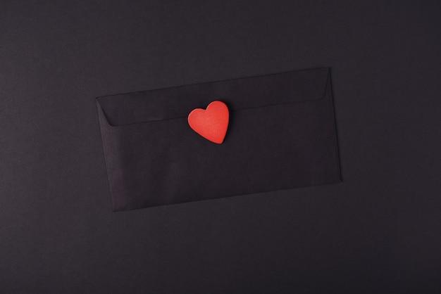 Zwarte envelop met een rood houten hart erop op de donkere (zwarte) achtergrond. valentijnsdag concept. plat lag, bovenaanzicht.