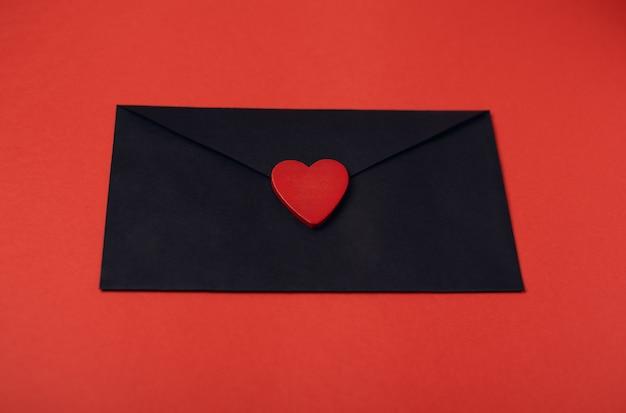 Zwarte envelop met het rode houten hart erop op de rode achtergrond. valentijnsdag concept.