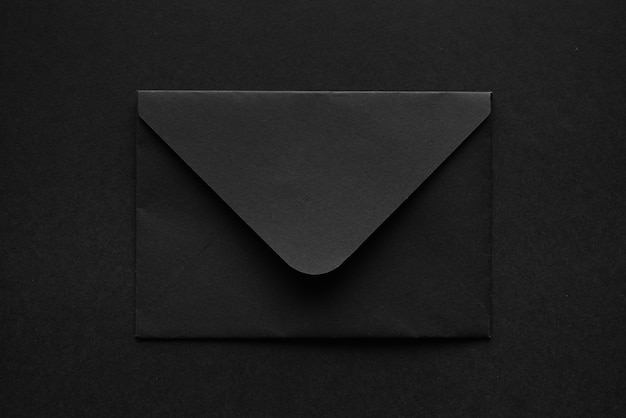 Zwarte envelop op een zwarte achtergrond.
