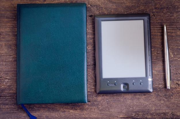 Zwarte ereader met notitieboekje en inktpen