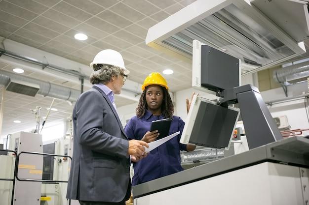 Zwarte fabrieksarbeider en haar mannelijke baas staan op industriële machine en praten
