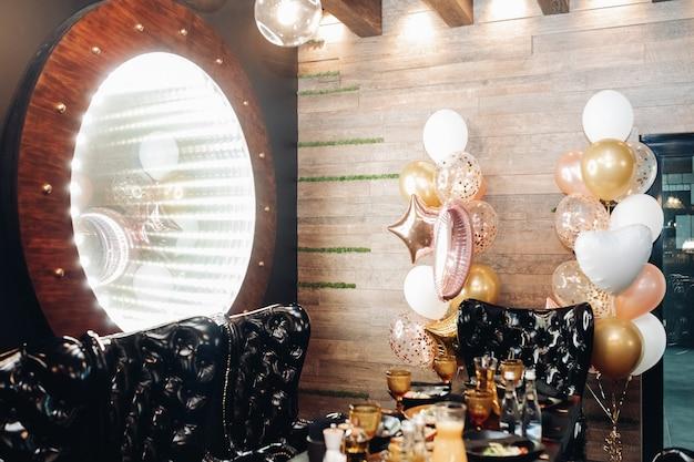Zwarte fauteuils bij de tafel en grote verlichte spiegel aan de muur. verijdelde ballonnen aan de muur. feestconcept