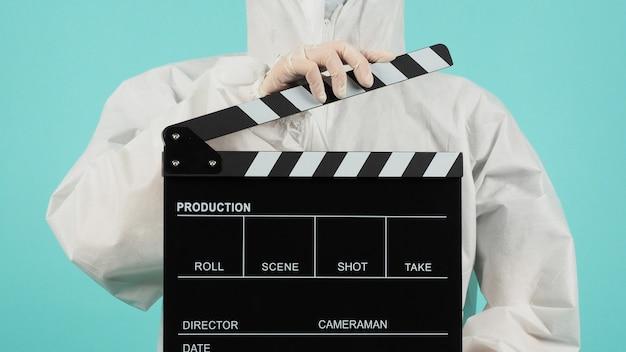 Zwarte filmklapper of film klepel bord. vrouw draagt gezichtsmasker en ppe pak op mintgroen of tiffany blue achtergrond.