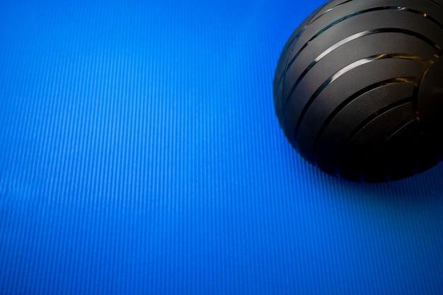Zwarte fitnessbal op blauwe mat backgorund