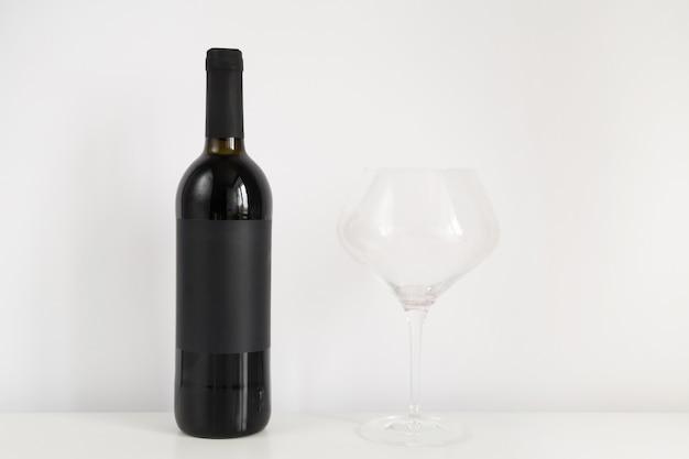 Zwarte fles rode wijn met glas op een witte achtergrond met kopieerruimte