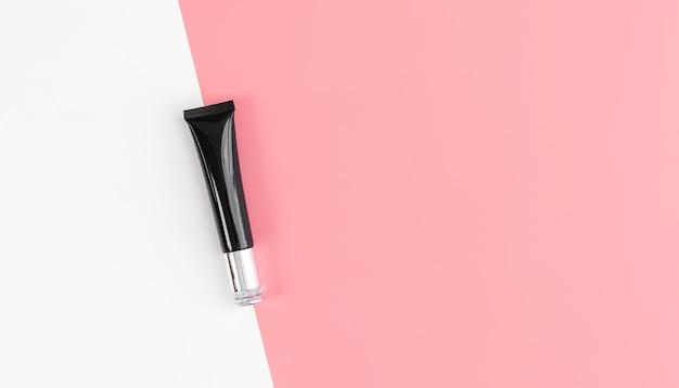 Zwarte flescrème, mockup van het merk schoonheidsproducten. bovenaanzicht op de roze achtergrond.