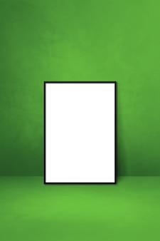 Zwarte fotolijst leunend op een groene muur. lege mockup-sjabloon