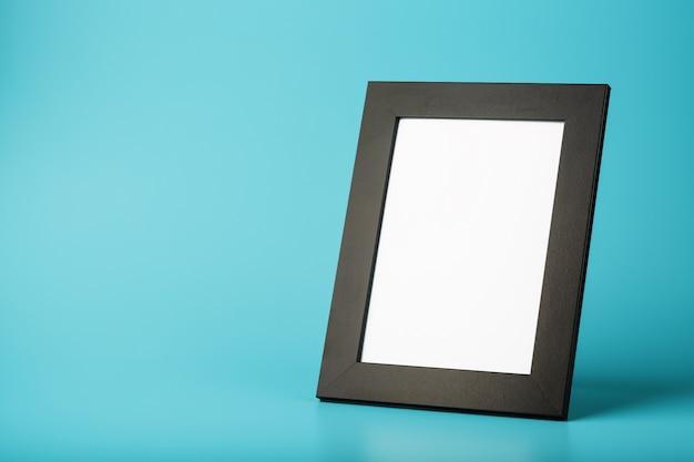 Zwarte fotolijst met vrije ruimte op een blauwe achtergrond.