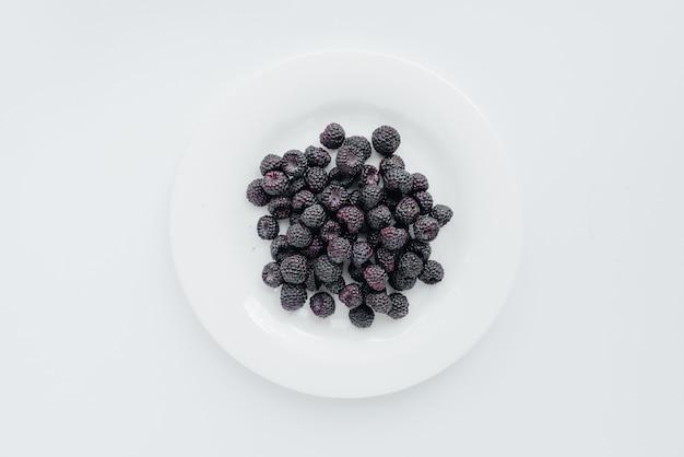 Zwarte frambozen bessen close-up op een wit oppervlak. gezonde voeding, natuurlijke vitamines. verse bessen.